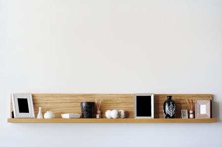 Stylish bookshelf on a white wall Foto de archivo