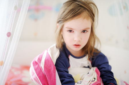 naptime: Little preschooler girl in pajamas on sunny morning Stock Photo
