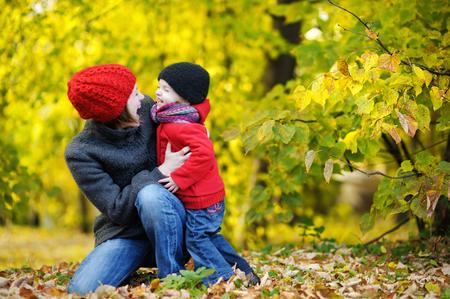 Madre joven y su muchacha del niño en los campos de otoño