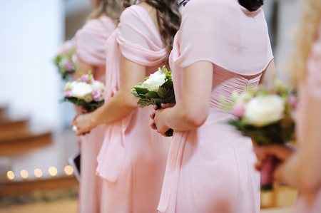 yellow dress: Row of bridesmaids with bouquets at wedding ceremony Stock Photo