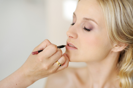 applying makeup: Young beautiful bride applying wedding make-up  by professional make-up artist Stock Photo