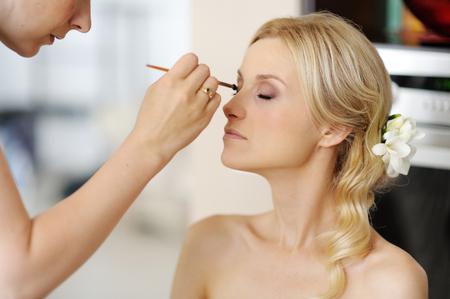 maquillaje de ojos: Joven y bella novia de la boda de aplicar el maquillaje por profesional del artista de maquillaje