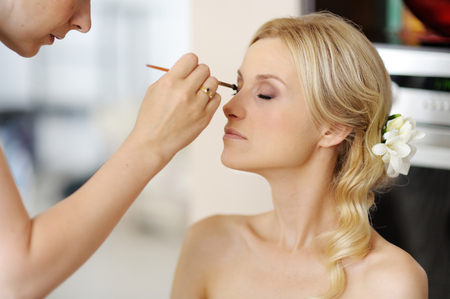 makeup a brush: Young beautiful bride applying wedding make-up  by professional make-up artist Stock Photo