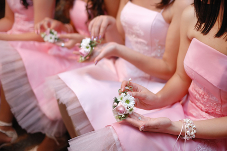purple dress: Row of bridesmaids with bouquets at wedding ceremony Stock Photo