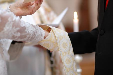 sotana: Boda: la novia y las manos del novio envueltos en la sotana del cura