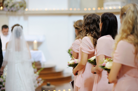 Row of bridesmaids with bouquets at wedding ceremony Stock Photo