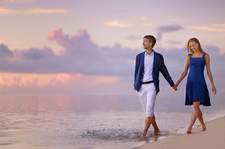 embracing couple: Beautiful romantic couple on a sunset on tropical beach Stock Photo