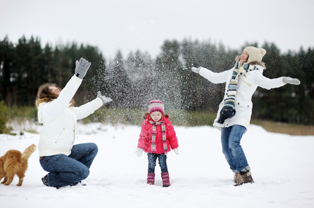 Happy family and a cat having fun on beautiful snowy winter day photo