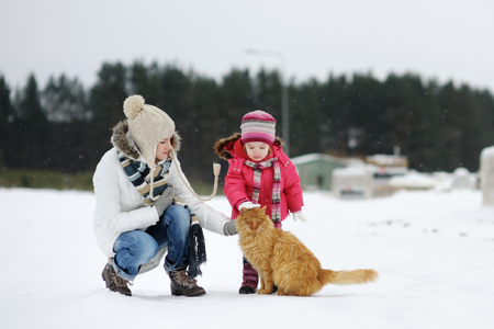 Toddler girl, her mother and a cat on beautiful snowy winter day photo