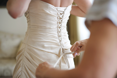 white dresses: Helping the bride to put her wedding dress on Stock Photo