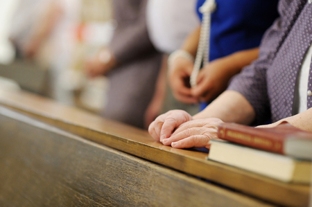 Hands of a senior woman while praying in a church Stockfoto