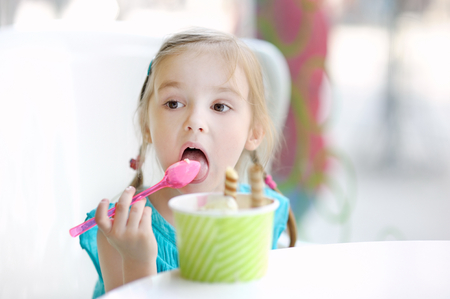 Adorable little girl eating ice cream at summer Stock Photo