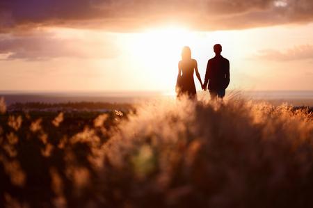 romance: Pares novos que apreciam o pôr do sol no prado