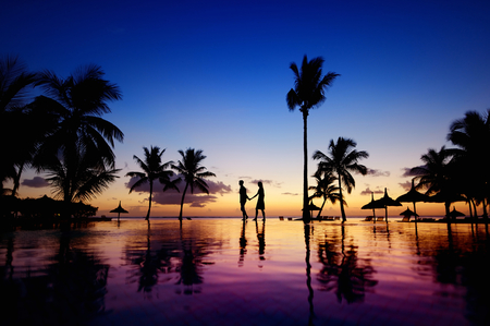 ロマンス: 熱帯のビーチの景色の日没で若いカップルのシルエット