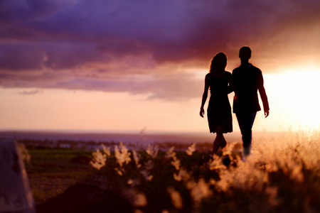 mujer enamorada: Joven pareja disfrutando de la puesta de sol en la pradera