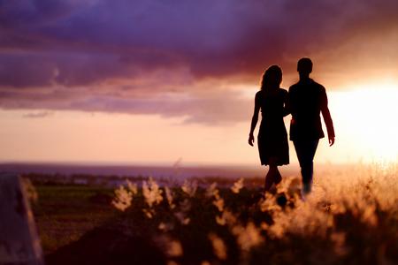 amor: Pares novos que apreciam o pôr do sol no prado