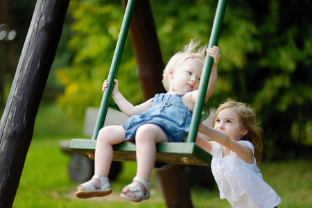 girl on swing: Two little sisters having fun on a swing on summer day Stock Photo