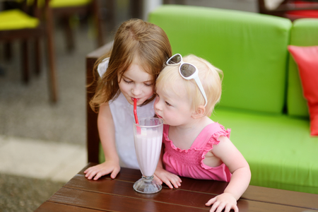 kid sitting: Two sisters drinking milkshake in outdoor cafe Stock Photo