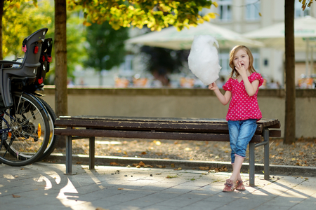 algodon de azucar: Adorable niña comiendo algodón de azúcar al aire libre en verano