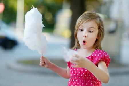 Schattig meisje eet candy-floss buiten in de zomer Stockfoto