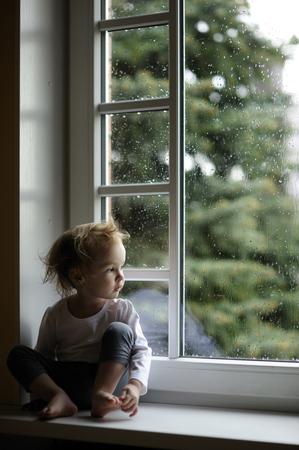 Muchacha adorable del niño que mira las gotas de lluvia en la ventana Foto de archivo