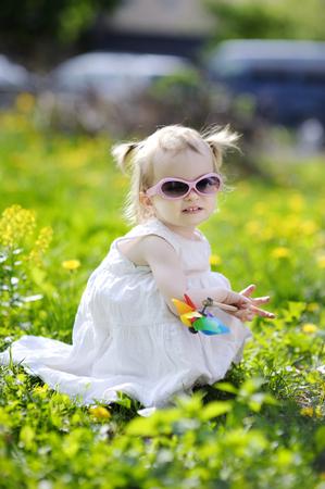 dandelion field: Adorable toddler girl sitting in dandelion field