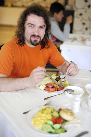 nice accommodations: Young man having his traditional breakfast Stock Photo