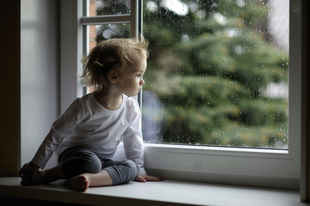 Adorable toddler girl looking at raindrops on the window Imagens