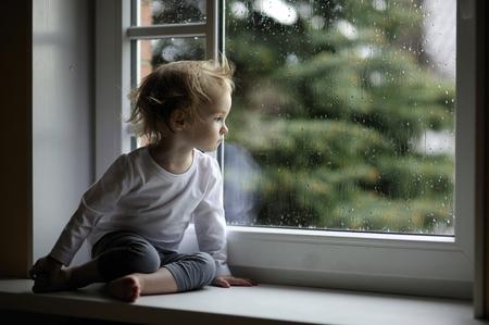 gotas de agua: Muchacha adorable del niño que mira las gotas de lluvia en la ventana Foto de archivo