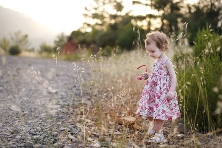 hairband: Adorable toddler girl in a beautiful floral dress Stock Photo