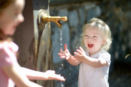grifos: Dos hermanas que se divierten con la fuente de agua potable en Italia