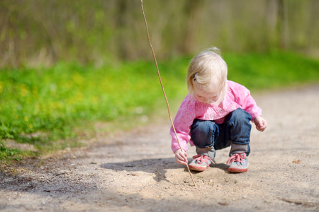 yard stick: Adorable little girl playing with a stick outdoors Stock Photo