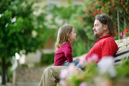 ni�os hablando: Padre e hija sentada en un banco hablando y riendo Foto de archivo