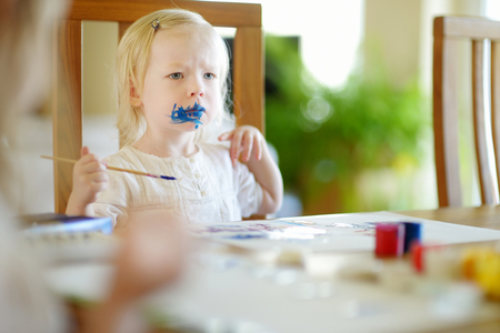 grimy: Funny grimy toddler girl painting in daycare