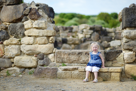 ancient architecture: Little girl sightseeing historical ruins of Nuraghi village