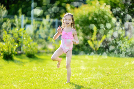 baby in suit: Little girl running though a sprinkler in a backyard Stock Photo