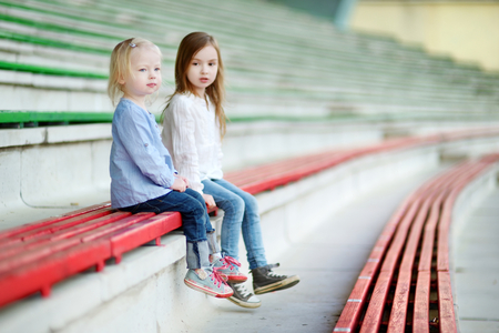 assigned: Two cute little sisters sitting on a stadium seats