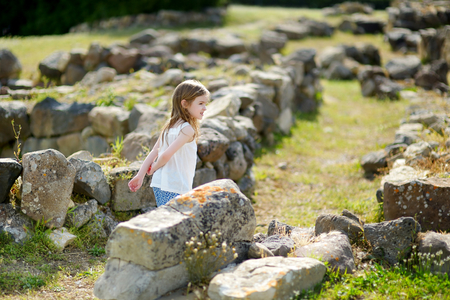 Little girl sightseeing historical ruins of Nuraghi village