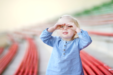 assigned: Cute little girl on a stadium Stock Photo