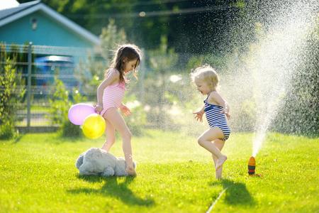 Little girls running though a sprinkler in a backyard
