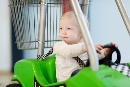Adorable little girl sitting in shopping cart