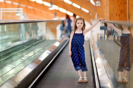 view of a staircase in a shop: Cute little child in shopping center standing on moving staircase Stock Photo