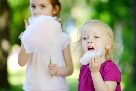 Adorable little sisters eating candy-floss outdoors at summer
