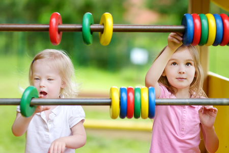 kinder: Two little sisters learning to count at a playground