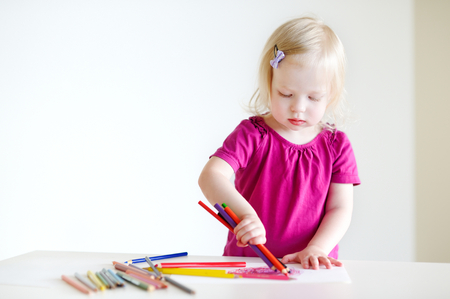 once person: Cute little toddler girl trying to draw a picture with several pencils at once