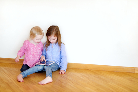 Two children playing on a digital tablet at home photo