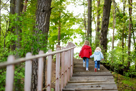 escalera: Dos pequeñas hermanas que caminan por las escaleras en el parque de verano en el hermoso día soleado