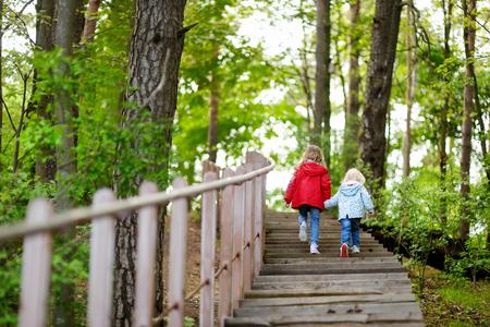 Duas irmãs pequenas que andam acima das escadas no parque do verão no belo dia ensolarado