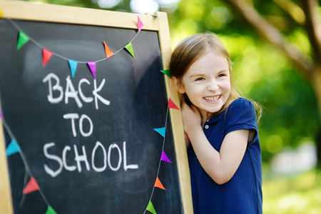 school uniform: Adorable little schoolgirl feeling extremely excited about going back to school