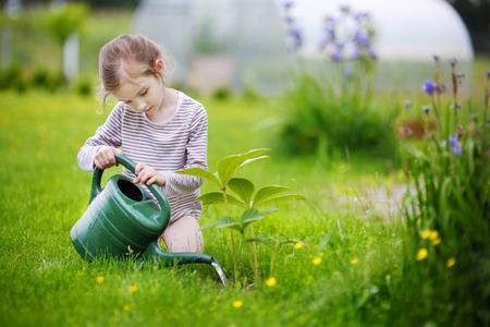 Riego de la chica linda de pequeñas plantas en el jardín